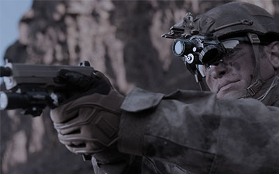 Armasight PVS-14 night vision monocular shown mounted on helmet while soldier aims with hand gun